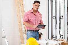 Happy contractor using a tablet Stock Image