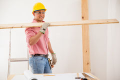 Happy contractor at work. Attractive Latin contractor carrying some wood while wearing protective equipment Royalty Free Stock Image