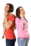 Happy conversation. Young man and woman talking on the mobile phones Royalty Free Stock Image