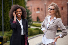 Happy conversation of two attractive businesswomen in the park. One woman is black. Happy conversation of two attractive businesswomen in the park. One women is Royalty Free Stock Images