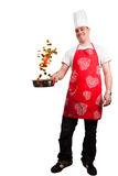 Happy cook. Guy cooking some fresh vegetables, isolated on white Royalty Free Stock Image