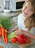 Happy cook. Girl learning to making the salad Royalty Free Stock Photos