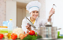 Happy  cook  in white uniform prepares  lunch Stock Image