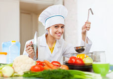 Happy  cook in white uniform tests soup Royalty Free Stock Photography