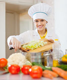 Happy  cook woman cooking vegetarian dinner. At commercial kitchen Stock Photo
