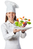 Happy cook woman holding a dish with floating vegetables Royalty Free Stock Photo
