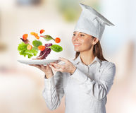 Happy cook woman holding a dish with floating vegetables on the kitchen Stock Photo