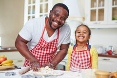 Happy cooking. Cheerful father and daughter cooking homemade pastry from yeast dough Royalty Free Stock Photography