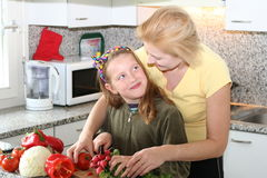 Happy cooking together. Woman cooking with her daughter together and cut different vegetables on the kitchen table royalty free stock images