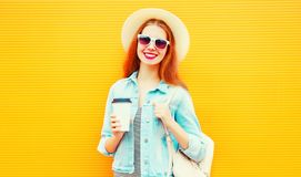 Happy cool girl with a coffee cup on orange background Royalty Free Stock Image