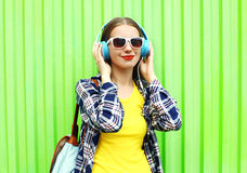 Happy cool girl listens to music in headphones over green Stock Photos