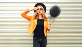 happy cool girl model blowing red lips sends air kiss, holding black air balloon stock photo