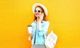 Happy cool girl talks on a smartphone with coffee cup Stock Photos