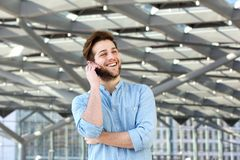 Happy cool guy talking on mobile phone stock photography