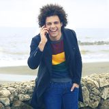 Happy cool man smiling talking on the phone in front of the ocean retro style Stock Photos