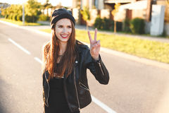 Happy cool teenage girl with long dark hair, wearing striped shirt, black leather jacket, beanie hat gesturing peace. Town street royalty free stock photography