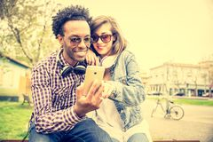 Happy coouple with mobile phone. Couple of multiracial lovers looking at smartphone and urban background - Stilish afroamerican guy and beautiful women watching Stock Image