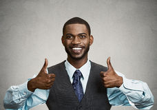 Happy corporate executive giving thumbs up gesture. Closeup portrait handsome young smiling business man, corporate employee giving thumbs up sign at camera Stock Photos