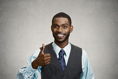 Happy corporate executive giving thumbs up gesture. Closeup portrait handsome young smiling business man, corporate employee giving thumbs up sign at camera Royalty Free Stock Images