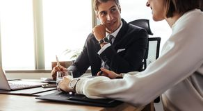Happy corporate professionals discussing over new project. Two happy corporate professionals having a meeting in office. Businessman and businesswoman working Stock Photo