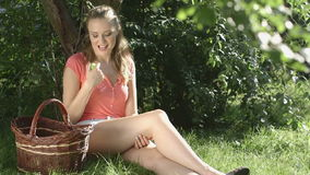 Happy Country Woman Eating Organic Apple in the Orchard.Basket of Apples. stock footage