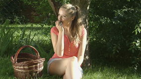 Happy Country Woman Eating Organic Apple in the Orchard.Basket of Apples. stock video footage
