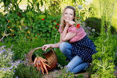 Happy countrywoman with a basket with carrots in her garden Stock Photo