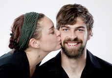 Happy couple. Young woman giving smiling man kiss on his cheek Royalty Free Stock Images