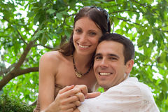 Happy Couple. A man and a woman smiling, a tree in background Royalty Free Stock Image