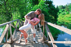 Happy couple. Young couple standing on wooden brifge among trees and kissing Stock Image