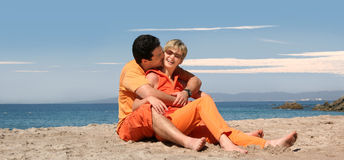 Happy couple. In orange clothes on the beach Royalty Free Stock Photography