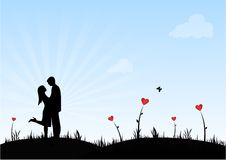 Happy Couple. A couple in a nature scenery surrounded by heart shaped flowers Stock Image