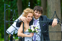 The happy couple. Leaning on the openwork fence of the old park is a pair of newlyweds Royalty Free Stock Photo