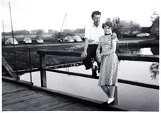 Happy couple 1956. Happy couple in 1956 in Germany on a bridge with old cars in the background Royalty Free Stock Photos