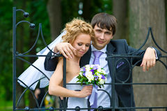 The happy couple_2. Leaning on the openwork fence of the old park is a pair of newlyweds Royalty Free Stock Photography