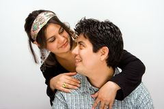 Happy couple. Couple looking at each other, she's standing behind him as he is sitting stock photo