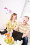 Happy couple. Smiling couple with laptop on a couch. She pouring coffee, he surfing in Internet. Relax at home Royalty Free Stock Photography