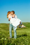 Happy couple. Happy young loving couple kissing outdoor in summertime Stock Image