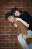 Happy couple. A happy young couple piggyback in front of brick wall royalty free stock photos