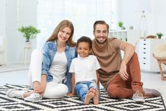 Happy couple with adopted African-American boy. Sitting on carpet at home Stock Photo