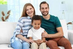 Happy couple with adopted African-American boy. Sitting on couch at home Royalty Free Stock Image