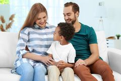 Happy couple with adopted African-American boy. Sitting on couch at home Stock Images