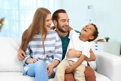 Happy couple with adopted African-American boy. Sitting on couch at home Royalty Free Stock Images