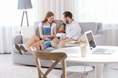 Happy couple with adopted African-American boy. Sitting on couch at home Stock Image