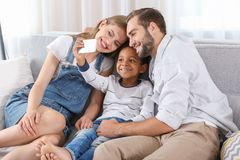 Happy couple with adopted African-American boy. Taking selfie while sitting on couch at home Royalty Free Stock Images