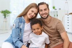 Happy couple with adopted African-American boy. At home Royalty Free Stock Images