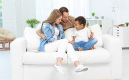 Happy couple with adopted African-American boy. Sitting on couch at home Royalty Free Stock Photos