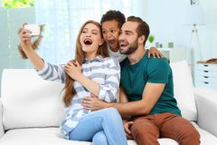 Happy couple with adopted African-American boy. Taking selfie on couch at home Royalty Free Stock Photos