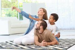 Happy couple with adopted African-American boy. Taking selfie at home Stock Image