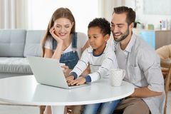 Happy couple with adopted African-American boy. Using laptop in living room Royalty Free Stock Image
